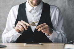 Crazy businessman eating smartphone. Crazy businessman about to eat smartphone with a knife and fork while sitting at wooden office desk with items Stock Photography