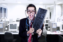 Crazy businessman hold keyboard at office. Crazy businessman hold keyboard and cables at office Stock Images
