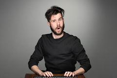 Crazy businessman sitting at table. On gray background.  hands on the keyboard Stock Images