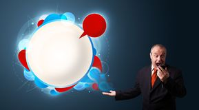 Businessman in suite holding a phone and presenting abstract modern speech bubble Stock Photography