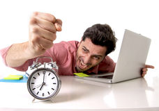 Crazy businessman switching off alarm clock sitting at office desk working with computer laptop in deadline project concept Stock Photography