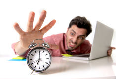 Crazy businessman switching off alarm clock sitting at office desk working with computer laptop in deadline project concept Royalty Free Stock Photo