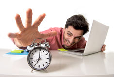 Crazy businessman switching off alarm clock sitting at office desk working with computer laptop in deadline project concept Royalty Free Stock Images