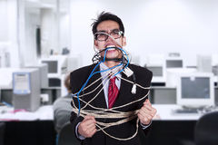 Crazy businessman tied in cable and rope at office stock images
