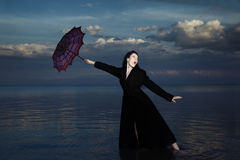 Crazy businesswoman. Businesswoman in the water with blown umbrella Stock Photography