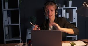 Crazy businesswoman enjoying music while working on laptop at night office. Crazy businesswoman dancing and singing song while working on laptop at night office stock footage