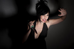 Crazy cannibal woman with blood on. Her face and knife in hands Stock Images