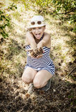 Crazy caucasian woman enjoying the pine cones in the forest by s Stock Photos