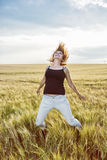 Crazy caucasian woman is jumping in the wheat field, beauty and Stock Photo