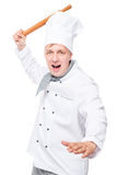 crazy chef attacking a wooden rolling pin on a white Stock Image