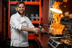 Crazy chef cooking with big fire on the frying pan Stock Image