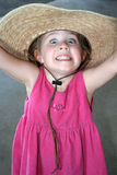 Crazy Child. A little girl in a hat shows her crazy face to the camera Royalty Free Stock Images