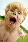Crazy Child with Painted Face. A litle boy growls at the camera with a painted face outside Royalty Free Stock Photography