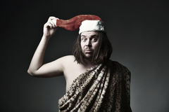 Crazy Christmas. Wild man in leopard skin wear Santa Claus hat Royalty Free Stock Photos