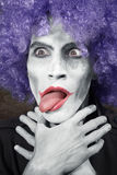 Crazy clown. Choking himself. Vertical photo. Artistic darkness and colors added stock photography