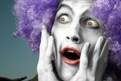 Crazy clown. Surprising clown with purple wig on a blue background royalty free stock image