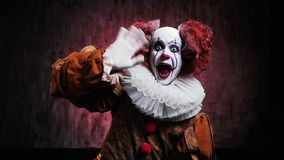 Crazy clown in colorful makeup suddenly jumps out from below. Crazy clown in colorful makeup and in a festive costume suddenly jumps out from below and laughs stock video
