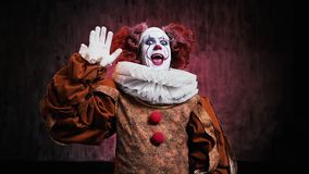 Crazy clown greeting and waving hand in front of the camera. Frightening clown in a festive costume is smiling at the camera. Shooting in slow motion on a dark stock video footage