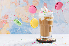 Coffee cocktail and macaroons. Crazy coffee cocktail and macaroons on wooden table royalty free stock photo