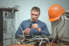 Computer repairman. Computer technician engineer. Support service. Crazy Computer network technician man is crimping a network cable by crimper tool in his royalty free stock image