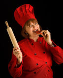 Crazy cook. Woman baker with rolling pin eatting cookie Stock Image