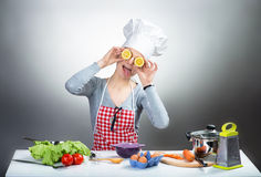 Crazy cooking woman with lemon eyes. Funny portrait of a fooling woman in chef's hat with lemon eyes, gray background stock image