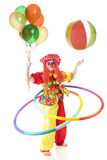 Crazy, Coordinated Clown. A happy clown wearing wild patterns and colors twirling two hula hoops while holding a bouquet of balloons and bouncing a beach ball in stock photos