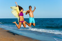 Crazy couple jump on beach. Royalty Free Stock Photography
