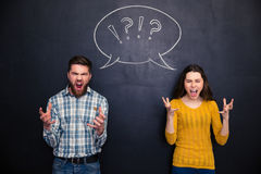 Crazy couple screaming over chalkboard background Stock Photos