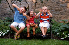 Crazy Cousins. Three young children sitting on a bench making silly faces. Could be spring or summer Royalty Free Stock Photography
