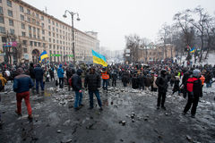 Crazy crowd of protesters walking in the burned square after fight with police in capital during anti-government riot in Kiev Stock Photo
