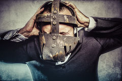Crazy, dangerous business man with iron mask and expressions Stock Photography