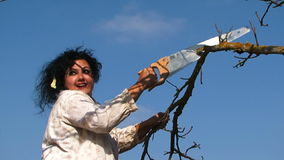 Crazy Dark-Haired Woman Sawing And Breaking A Tree. Two frames: waist up shot of a crazy plus-sized dark haired woman with mess on her head in white shirt and stock video