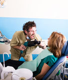 Crazy dentist patient at the dentist, the patient is terrified Royalty Free Stock Photography