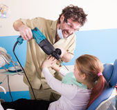 Crazy dentist treats teeth of the unfortunate patient. The patient is terrified. Stock Photo