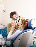 Crazy dentist treats teeth of the unfortunate patient. The patient is terrified. Royalty Free Stock Photos