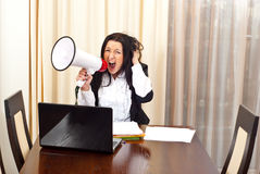 Crazy desperate woman shouting megaphone. Crazy desperate business woman shouting megaphone and sitting on chair in a meeting room royalty free stock images