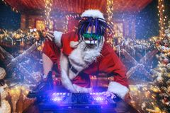 Crazy dj santa. Ð¡razy punk Santa Claus in luminous glasses and headphones holds a party near his house decorated with lights. Christmas cool party stock photos