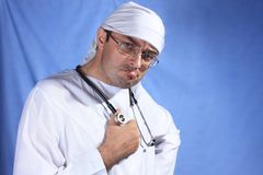 Crazy doctor. With stethoscope on blue background Royalty Free Stock Photo