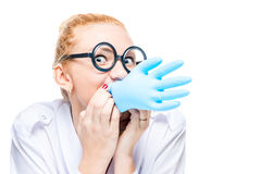 Crazy doctor blows a blue glove. Portrait is isolated Royalty Free Stock Photos