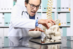 Crazy doctor with skull in office Stock Photography