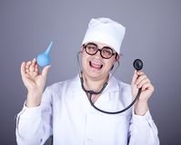 Crazy doctor with a stethoscope and enema. Stock Image