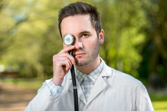 Crazy doctor with stethoscope instead his eye Stock Photos