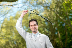 Crazy doctor waving stethoscope overhead Stock Photo