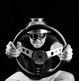 Crazy Driver. Portrait of a man wearing a collander on his head and holding a steering wheel Royalty Free Stock Images