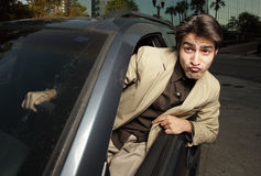 Crazy driver. Young businessman driving with his head out of the car window Stock Photos