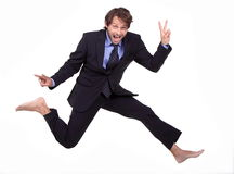 Crazy dude. In a suit, is jumping barefoot and making v-sign Stock Images