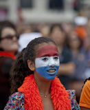 Crazy Dutch soccer fan in orange and with national colors on her face Stock Photography