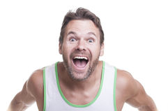Crazy excited man. Bearded muscular Caucasian man in tank top leans forward at camera and yells with extreme excitement on white background Stock Photography