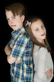 Crazy facial expression portrait of young boy & girl black back Stock Photography
